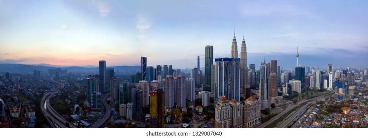 KUALA LUMPUR, MALAYSIA - FEBRUARY 3, 2019: Panoramic aerial view of Kuala Lumpur city skyline during hazy sunrise.
