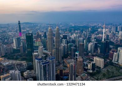 KUALA LUMPUR, MALAYSIA - FEBRUARY 3, 2019: Aerial view of Kuala Lumpur city skyline during hazy sunrise.