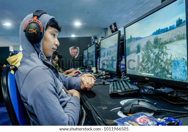 KUALA LUMPUR, MALAYSIA - JANUARY 14, 2018. Unidentified e-Sport players participating in Online Cyber Games Tournament at the cyber cafe in Kuala Lumpur. Low light and high ISO photography.