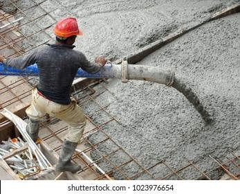 KUALA LUMPUR, MALAYSIA -JANUARY 16, 2018: Construction workers pouring wet concrete using concrete spider hose into floor slab form work at the construction site.