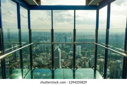 KUALA LUMPUR / MALAYSIA - JANUARY 2019:  Impressive city aerial view from Skybox transparent glass balcony in Menara KL tower, a famous tourist viewpoint at 400 meters height