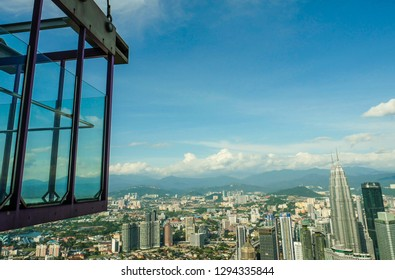 KUALA LUMPUR / MALAYSIA - JANUARY 2019:  Impressive city aerial view at Skybox transparent glass balcony in Menara KL tower, a famous tourist viewpoint at 400 meters height
