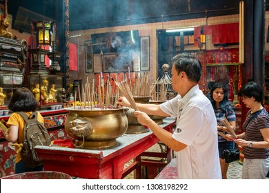 Kuala Lumpur, Malaysia. January 2019.   Faithful pray in froint of the altar in Sin Sze Si Ya Temple