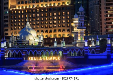 Kuala Lumpur, Malaysia: January 25, 2018: Office buildings and Sultan Abdul Samad Jamek Mosque with water fountain lit at night on the banks of the Klang and Gombak rivers.