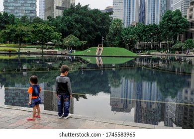KUALA LUMPUR, MALAYSIA - JANUARY 26TH, 2020 : Children stand near a cliff of a pool with a nice reflection at a mall in Kuala Lumpur, Malaysia.
