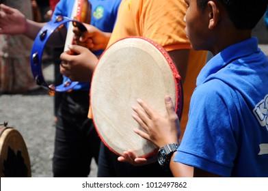 KUALA LUMPUR, MALAYSIA -JANUARY 27, 2018: Boy plays Kompang during Malay wedding ceremony. Kompang is a Malay traditional drums that usually played during the traditional Malay wedding