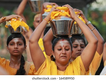 Kuala Lumpur, Malaysia, January 27 2013: A Hindu devotee carry a pot of milk each during Thaipusam festival to fulfill their vows and offer thanks to the deities.