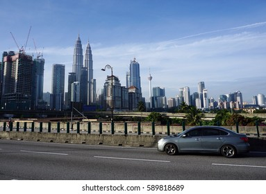KUALA LUMPUR, MALAYSIA - JANUARY 29, 2017: A car drive passed Kuala Lumpur city center iconic building KLCC at the Jalan Tun Razak highway on Sunday morning.