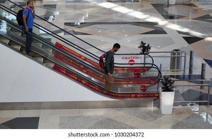 Kuala Lumpur, Malaysia - January 30 2018: Unidentify middle east tourist walking down thru escalator into departure area at the airport