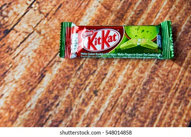 KUALA LUMPUR, MALAYSIA - JANUARY 30, 2016: KitKat Green Tea Chololate Wafer Snack from Malaysia. Kit Kat bar green tea flavor isolated on wood. Kit Kat is a chocolate biscuit bar confection by Nestle