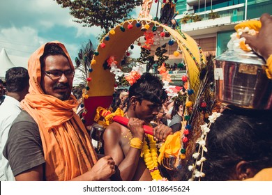 KUALA LUMPUR, MALAYSIA - JANUARY 31, 2018: Hindu man carries small kavadi with support. Devotees celebrate Thaipusam festival with procession and offerings. Trial concept.