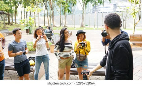 Kuala lumpur  , Malaysia - January 5 , 2018,  group of young student photographer taking pictures on photography shooting workshop course outdoor