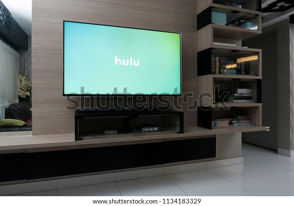 KUALA LUMPUR, MALAYSIA - JULY 15TH, 2018 : Modern lifestyle with LG Android TV to stay connected & browsing media using favourite Apps. Tv display Hulu app over green background.
