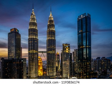 Kuala Lumpur, Malaysia - July 18, 2018: The Petronas Towers sit as the centerpiece of the skyline above the KLCC center on a blue, gold, and pink sunset night in the background