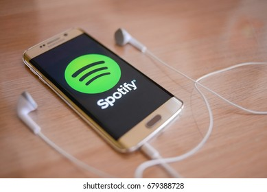 KUALA LUMPUR, MALAYSIA - JULY 18, 2017: Spotify is a music service that offers legal streaming music. Smartphone opening spotify app on wooden table.