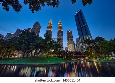 Kuala Lumpur, MALAYSIA - July 19, 2019: Clear blue sky sunset at KLCC Park with the lake in the foreground and the majestic Petronas Twin Towers and other skyscrapers in the background.