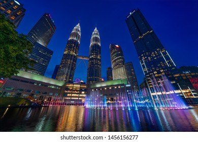 Kuala Lumpur, MALAYSIA - July 19, 2019: Clear blue sky sunset at KLCC Park with musical fountains in the foreground and the majestic Petronas Twin Towers and other skyscrapers in the background.
