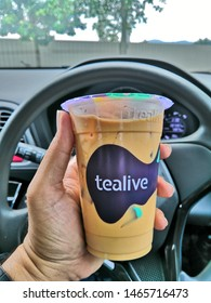 Kuala Lumpur, Malaysia - July 2019 : Closeup hand holding Tealive Signature Brown Sugar Milk Ice Tea with background in the car. Tealive is a Taiwanese global franchise teahouse chain based in Taiwan.