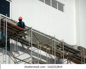 KUALA LUMPUR, MALAYSIA -JULY 23, 2018: Construction workers plastering wall using cement plaster at the construction site. They are wearing appropriate safety gear to prevent bad happen.