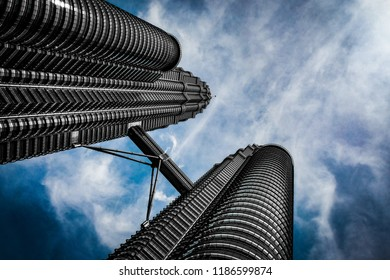 Kuala Lumpur, Malaysia - July 28, 2018:  The Petronas Towers modern architecture of glass and steel against a sunny, cloudy, blue sky background