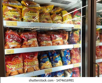 KUALA LUMPUR, MALAYSIA -JULY 28, 2019: Packed chicken nugget in various brand placed in display chiller refrigerator inside the huge supermarket.