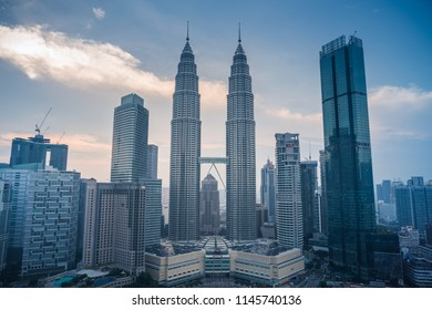Kuala Lumpur, MALAYSIA - July 30, 2018 : Petronas Twin Towers (fondly known as KLCC) and the surrounding buildings at sunset seen from the Skybar at Traders Hotel.