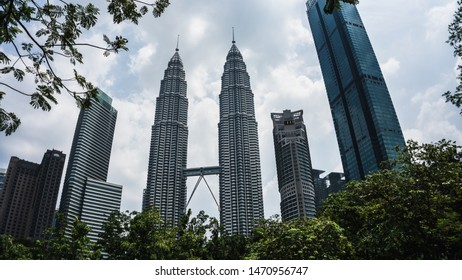 Kuala Lumpur, Malaysia - July 30, 2019: Low angle view of the famous Petronas Twin Tower or KLCC from the green tree nature and surrounding with tall skyscraper and cloudy sky.