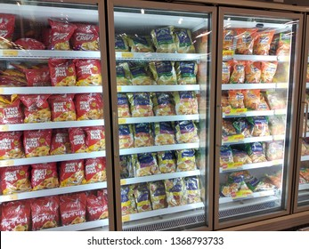 KUALA LUMPUR, MALAYSIA -JULY 4, 2019: Packed chicken nugget in various brand placed in display chiller refrigerator inside the huge supermarket.