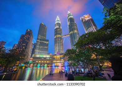 Kuala Lumpur, Malaysia - July 7, 2018: Tourist and local at Petronas Twin Towers KLCC Lake Park with musical fountain during sunset dusk.