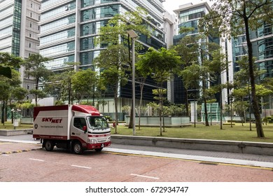 KUALA LUMPUR, MALAYSIA - JULY 7 2017. A SkyNet delivery truck parked at the side of a stone-paved road during daytime delivery. SkyNet is amongst the biggest delivery couriers in Southeast Asia