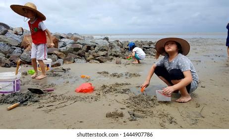 Kuala Lumpur , Malaysia - July 8 2019: Asian kids playing on a beach of Morib, Banting, Malaysia
