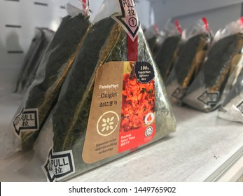 KUALA LUMPUR, MALAYSIA - JULY 9, 2019 : Rows of halal onigiri sold at Family Mart store. Onigiri consists of rice ball in triangular shape, stuffed with various fillings and wrapped in seaweed.