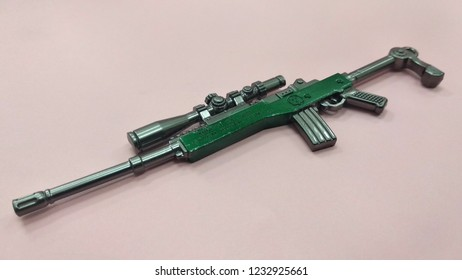 KUALA LUMPUR, MALAYSIA -JUNE 09, 2018: A miniature model of military sniper automatic gun in small-scale isolated on red background. Sale as a collector item for military gear collector and hobbyist.
