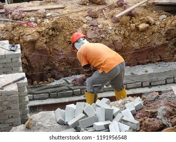 KUALA LUMPUR, MALAYSIA -JUNE 1, 2018: Bricklayer lay sand brick and stacked it together using cement mortar to form monsoon drain wall at the construction site. Necessary tools required for this job.