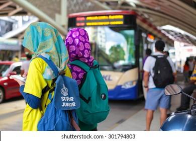 KUALA LUMPUR, MALAYSIA- JUNE 13, 2015 : Muslim teenagers waiting for their bus at bus station near Chinatown, Kuala Lumpur Malaysia.