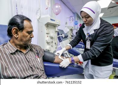 KUALA LUMPUR, MALAYSIA - JUNE 14, 2013. Nurse helping her patient donating blood at the National Blood Center in Kuala Lumpur.