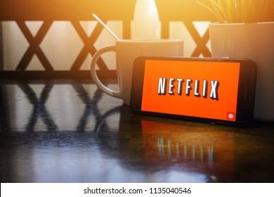 Kuala Lumpur, Malaysia - June 16, 2018:  Smartphone displaying word Netflix on wooden table with selective focus and crop fragment