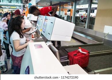 KUALA LUMPUR, MALAYSIA, JUNE 18, 2018: Passenger using convenient self check-in luggage bag machine at KL International Airport facility