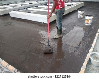KUALA LUMPUR, MALAYSIA -JUNE 25, 2017: Waterproofing membrane applied by construction workers on top of concrete slab. Waterproofing layer to prevent water from entering below of the concrete slab.
