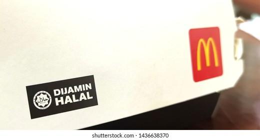 "Kuala Lumpur, Malaysia- June 28 2019: Dijamin Halal logo on MacDonalds burger pack. Halal is an Islamic Arabic term meaning ""permissible""."