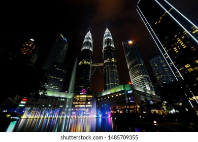 KUALA LUMPUR, MALAYSIA - JUNE 28, 2019: Beautiful night scenery of Petronas Twin tower and Suria KLCC with colorful fountain and reflection in the pool.