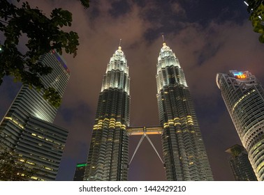Kuala Lumpur, Malaysia - June 30th 2019: KL Petronas Twin Towers with view of elevated bridge lighted up at dusk. Low angle view from KLCC Park.
