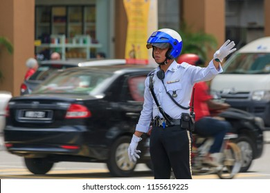 Kuala Lumpur, Malaysia - June 5 2014: Traffic police officer regulating the traffic at intersection Jalan Pudu / Jalan Imbi