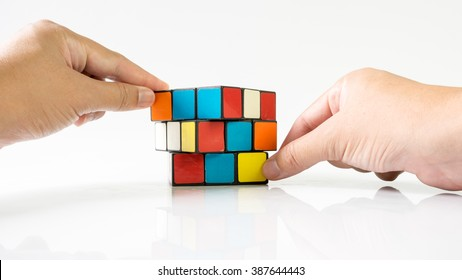 Kuala Lumpur, Malaysia - March 08, 2016: Hands playing Rubik's Cube on a white background. This famous cube puzzle was invented by the architect Erno Rubik in 1974