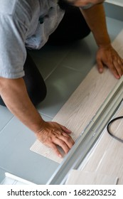 Kuala Lumpur, Malaysia - March 1, 2020: A man installing new vinyl tile floor, a DIY home project.