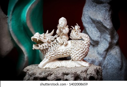 Kuala Lumpur, Malaysia - March 12, 2019: Small statuette of Qilin carrying baby on his back in the Taoist temple of Guan Di Temple.