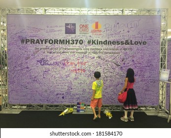 KUALA LUMPUR, MALAYSIA - MARCH 14, 2014: two kids signing a billboard for the safe return of Malaysia Airlines MH370 which went missing on March 8 2014. MH370 remains missing to date