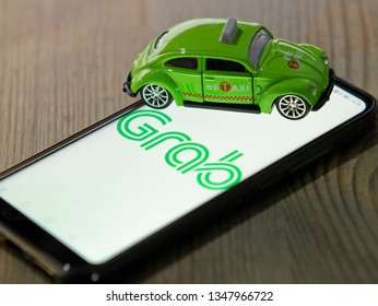 KUALA LUMPUR, MALAYSIA - march 24, 2019 : grab car apps and green taxi toy car, Grab Car, high demand for public transport in Malaysia.