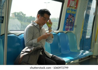 Kuala Lumpur, Malaysia - March 8th, 2018 : Chinese man with his smartphone while waiting to his destination in MRT (Mass Rapid Transit).