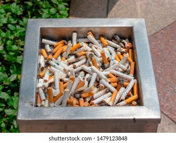 Kuala Lumpur, Malaysia - Mart 11,2019: Cigarette butts with ashes in street ashtray at smoking area in asia. Ashtray full of old cigarette and cigar butts. Unhealthy lifestyle and addiction background